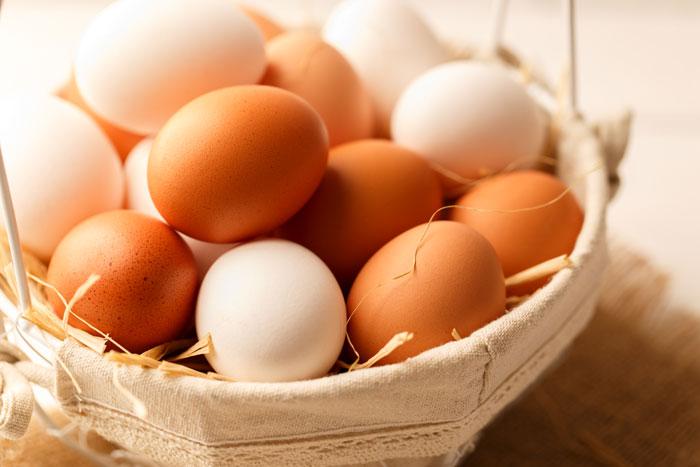 weiße und braune Eier liegend in einem Körbchen